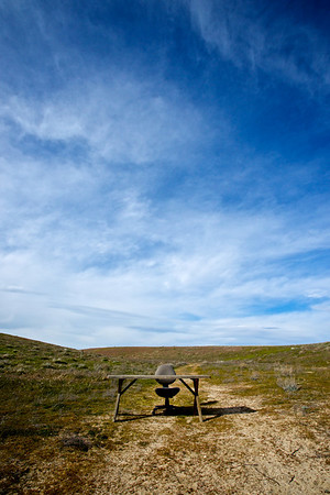 A random chair and desk grace an otherwise empty wilderness.