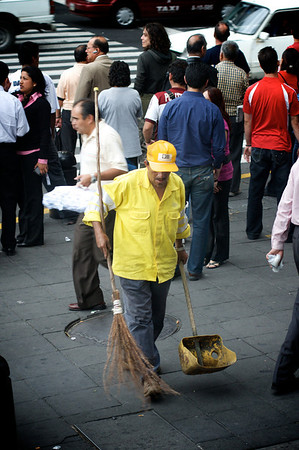 MEXICO CITY - AUGUST 5, 2008: A Mexican street cleaner plies his trade with an antique broom on the sidewalks of Mexico City, Mexico.