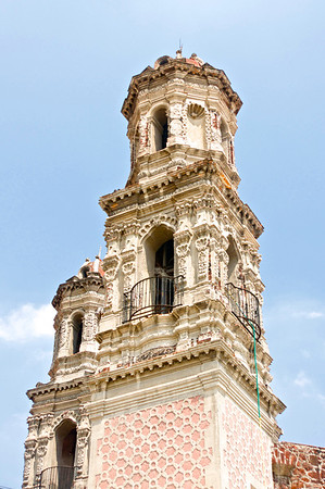 A Catholic church spire rises above the streets of Mexico City.