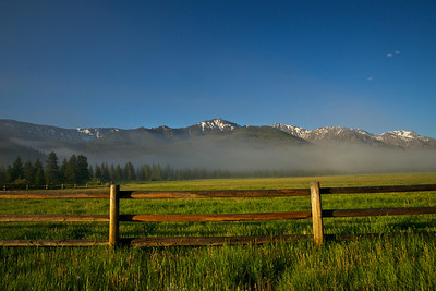A wooden rail fence surrounds a green grassy meadow in the mountains of northern Wyoming.
