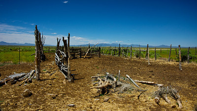 An old western horse corral lies vacant on a vast plain in the American West.