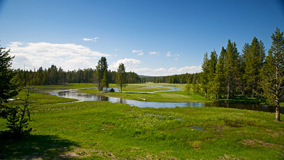 A blue river reflects the blue sky as it winds through Yellowstone National Park.